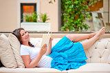 brunette on white sofa reading a book