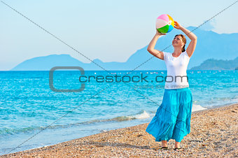 girl plays with a beach ball near the sea