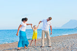 parents shake their little son on the beach