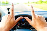 male hands on the steering wheel with protruding fingers