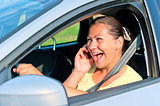 beautiful girl behind the wheel with phone laughing