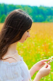 portrait of a young brunette in a field of daisies