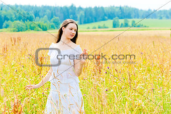charming brunette in a field of yellow flowers