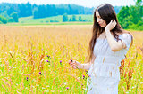 portrait of a beautiful young brunette in a field