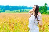 Russian beautiful woman in field with flowers