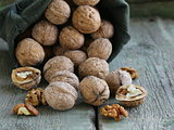 linen bag with walnuts on wooden background