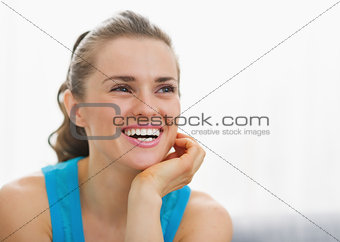 Portrait of smiling young woman sitting in living room