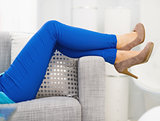 Closeup on leg of young woman laying on couch