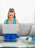 Happy young woman sitting in living room and using laptop