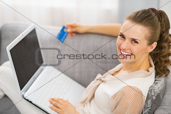 Portrait of smiling young housewife with credit card and laptop