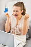 Happy young housewife with credit card and laptop rejoicing