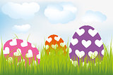 Easter background with heart-decorated eggs in meadow