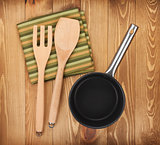 Frying pan and kitchen utensils on wooden table
