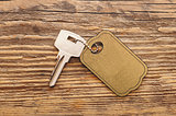 silver key with blank tag wooden background. space for your text