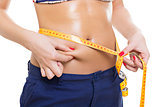 Fit woman pinching fat and measuring belly
