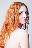 Closeup half-turned portrait of beautiful smiling redhead girl