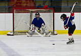 Ice hockey player shoots the puck at the net