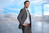 Composite image of serious businessman with hand on hip