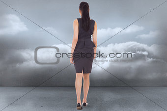 Composite image of businesswoman walking