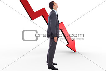Composite image of happy businessman with hand in pocket