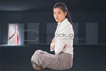Composite image of businesswoman sitting cross legged with arms crossed