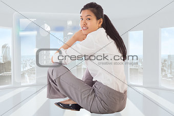 Composite image of businesswoman sitting cross legged smiling