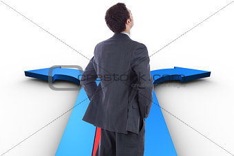 Composite image of businessman standing with hands on hips