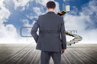 Composite image of businessman standing with hand on hip