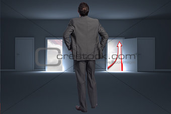 Composite image of businessman with hands on hips