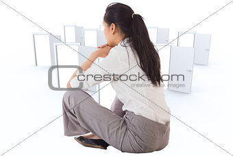 Composite image of businesswoman sitting cross legged