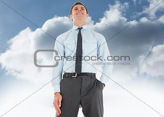 Composite image of happy businessman standing with hand in pocket