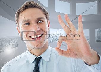 Composite image of businessman showing ok sign