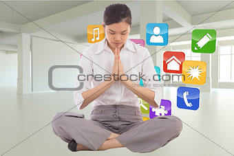 Composite image of businesswoman sitting in lotus pose