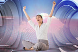 Composite image of businesswoman sitting cross legged cheering