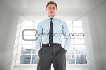 Composite image of serious businessman standing with hands in pockets