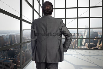 Composite image of businessman with hand on hip