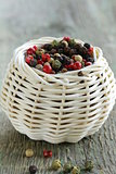 colorful peppercorn in wicker bowl on wooden table