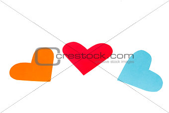 Three paper colored heart shapes on a white background
