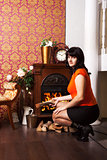 young beautiful woman sits near the fireplace