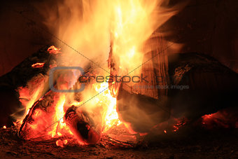 Bright fire in the fireplace. Burning wood photographed close.