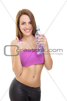 Fit young woman holding bottle of water showing thumb up