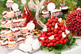 Sweet bar with cupcakes, fresh strawberries, and cherries