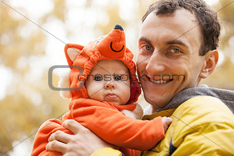 Young Caucasian man and his little son in fox costume in autumn park