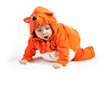 Baby boy in fox costume looking down with surprise over white