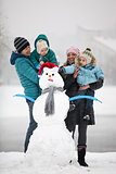 Caucasian family with two sons beside snowman outdoors
