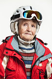 Senior woman wearing ski jacket and goggles on snowy slope in mountains. With clipping path.