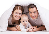 Young family with baby boy under blanket on bed