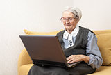 Senior woman using laptop computer while sitting on sofa