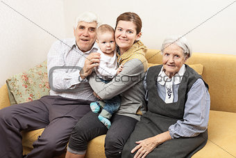 Four generation family sitting on sofa at home