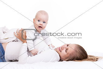 Smiling young woman holding baby son while lying on back